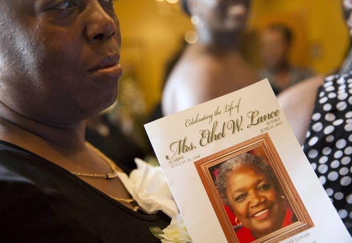 Imagen de una mujer que sostiene el programa para el servicio fúnebre de Ethel Lance, de 70 años, una de las nueve personas que murieron en el tiroteo en la iglesia Emanuel en Charlesto, Carolina del Sur.  (AP Photo/David Goldman)