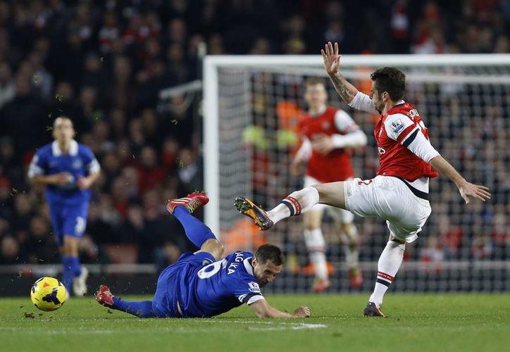 Olivier Giroud, del Arsenal, en duelo por la pelota con Phil Jadielka del Everton, durante el encuentro de hoy en el Estadio Emirates de Londres. (Agencias)