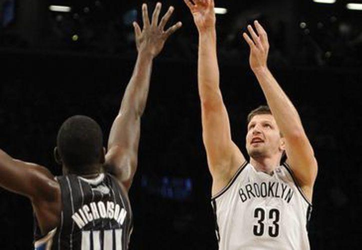 El bosnio Mirza Teletovic (33), de los Nets de Brooklyn, dispara delante de Andrew Nicholson (44), del Magic de Orlando. (AP)