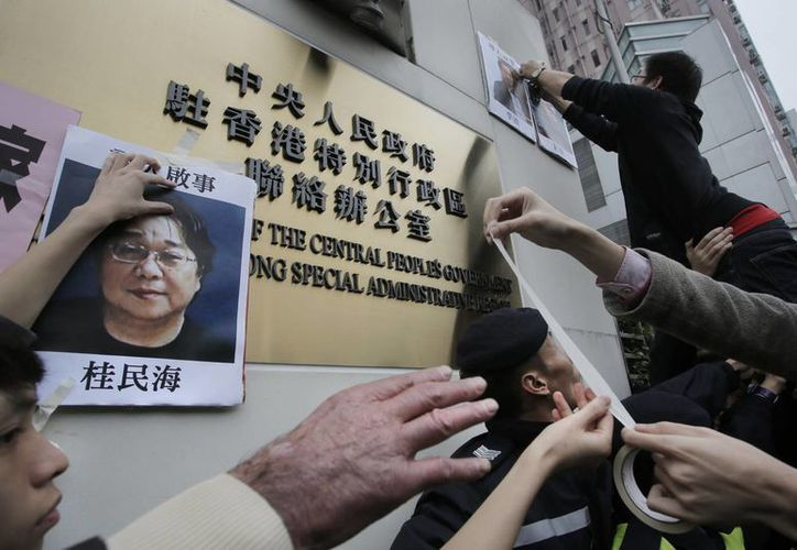 Manifestantes intentan colocar fotografías de editores desaparecidos durante una protesta ante la oficina de Enlace del Gobierno Popular Central en Hong Kong. (Agencias)