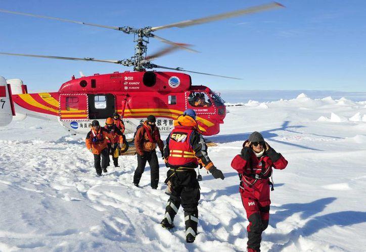La agencia noticiosa oficial china Xinhua muestra a un primer grupo de pasajeros que habían quedado atascados a bordo del barco ruso MV Akademik Shokalski a su llegada a un lugar seguro en la Antártida. (Agencias)