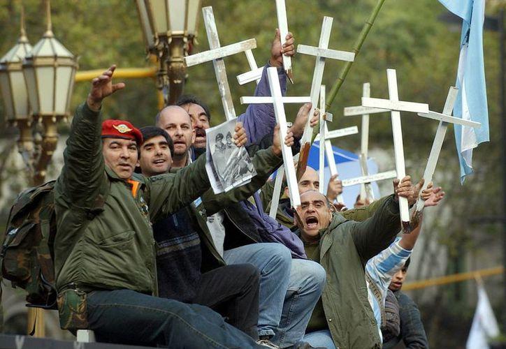 Foto de combatientes de la Guerra de Malvinas, librada en el año 1982 contra Inglaterra, durante un protesta en la que portaron cruces blancas con los nombres de sus compañeros caídos, durante la fiesta popular por el Día de la Patria. (Archivo/EFE)