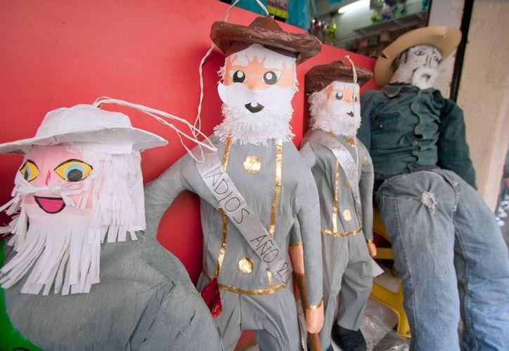 Los tradicionales muñecos 'de Año Viejo' esperan 'pacientes' la hora final. La tradición de quemarlos tiene unos 30 años en Yucatán. La imagen corresponde a piñatas que cumplen el mismo propósito que los muñecos. (Notimex)