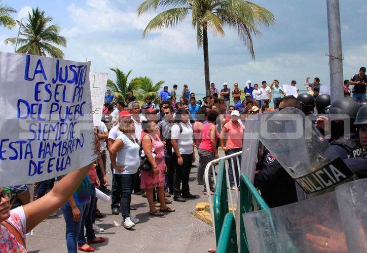 Poco más de 300 manifestantes se enfrentaron a policías antimotines ayer a las puertas del Congreso del Estado, en Chetumal. (Ángel Castill/SIPSE)