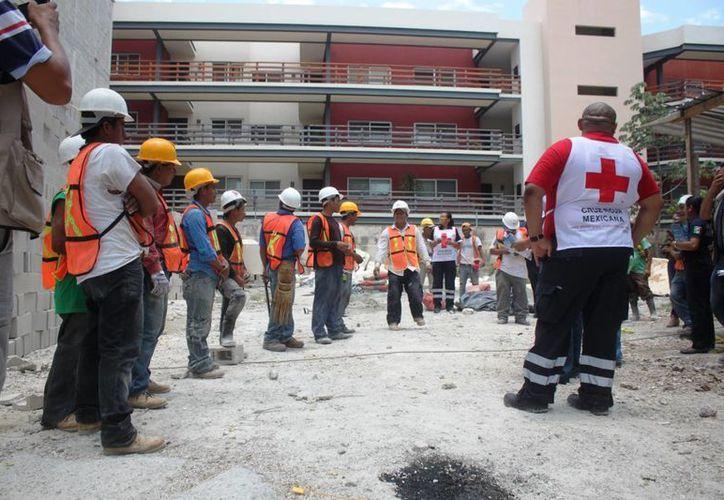 Elementos de cuerpos de rescate instruyeron a trabajadores de la construcción sobre los riesgos de no hidratarse debidamente. (Daniel Pacheco/SIPSE)