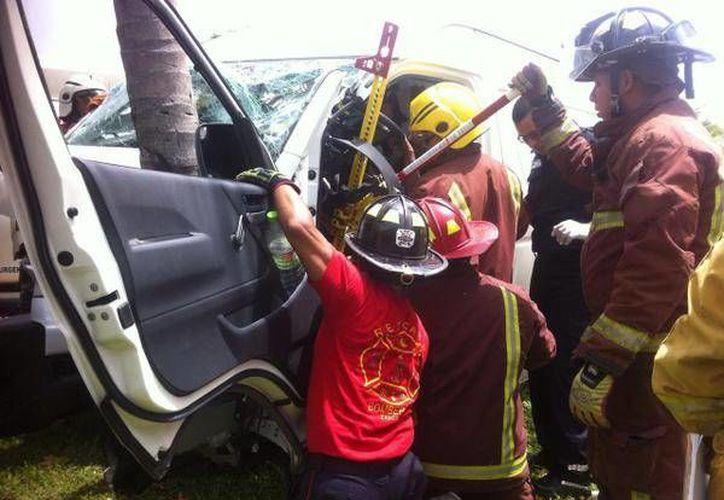 El Cuerpo de Bomberos realizó el rescate de las personas que quedaron prensadas al interior del vehículo. (Sergio Orozco/SIPSE)