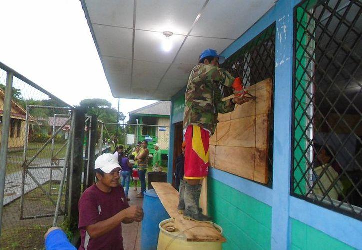 Algunas escuelas de Nicaragua funcionaron como albergues ante la llegada de 'Otto' al país. Imagen edida por Erick Morales donde se observa cómo los ciudadanos aseguraban un colegio antes de la llega del huracán. (EFE/Erick Morales)