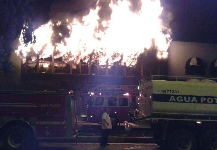 El incendio del sábado en la noche, en el momento en que las llamas consumen el primer piso de Galerías El Triunfo. (Licety Díaz/SIPSE)