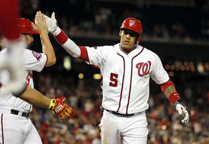 Los Nacionales de Washington derrotaron 5-3 a los Dodgers de Los Angeles al completar un juego que fue suspendido. En la imagen Yunel Escobar celebra un jonrón con Tanner Roark. (AP)