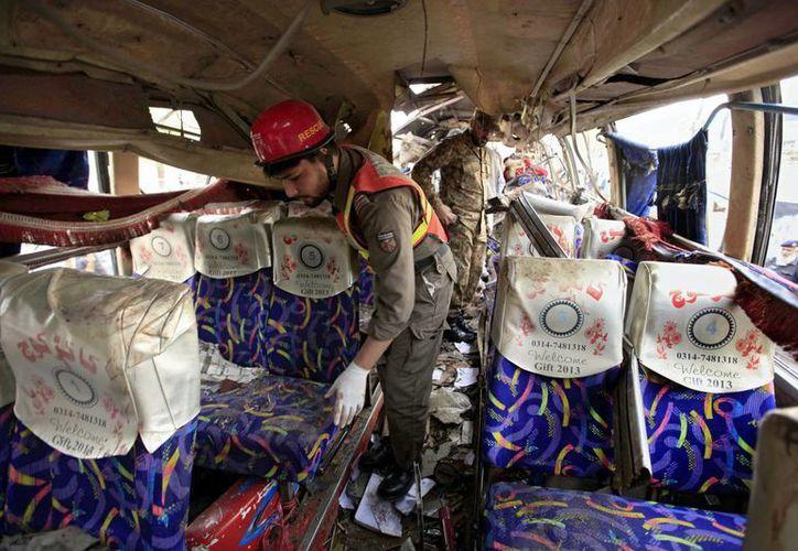 Miembros de los equipos de rescate inspeccionan un autobús que sufrió un atentado con bomba en Peshawar, Pakistán. (EFE)