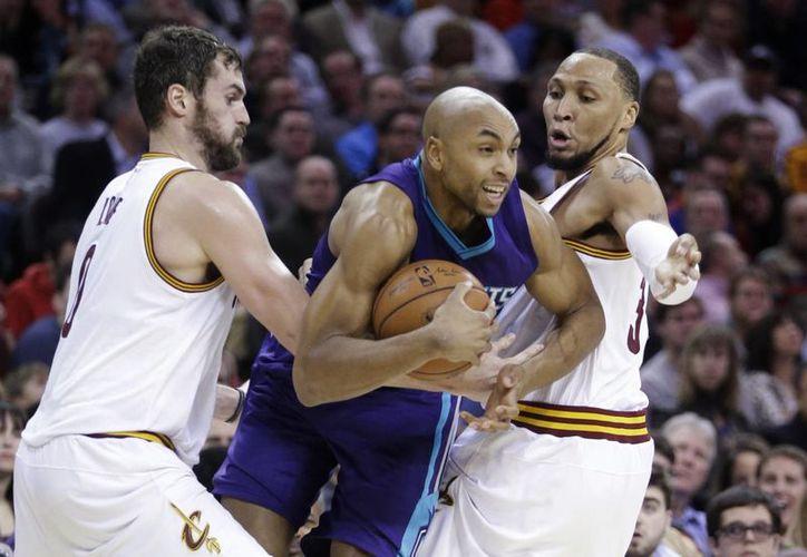 Gerald Henderson (c), de Charlotte, trata de pasar entre Kevin Love y Shawn Marion en duelo ganado por Cavaliers de Cleveland en la NBA. (Foto: AP)