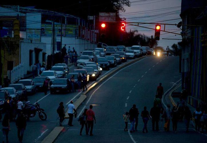 Peatones y conductores son bloqueados por una protesta de los residentes del municipio El Hatillo, que están obstruyendo las calles por los cortes de luz que hay en Venezuela. (Agencias)