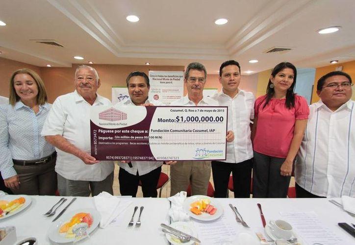 En presencia de los directores de planteles de educación, los directivos de la Fundación Cozumel recibieron simbólicamente un cheque por un millón de pesos. (Gustavo Villegas/SIPSE)