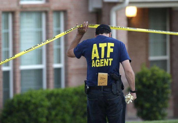 Un agente de la ATF en la escena donde se realizó uno de los tiroteos. (Agencias)