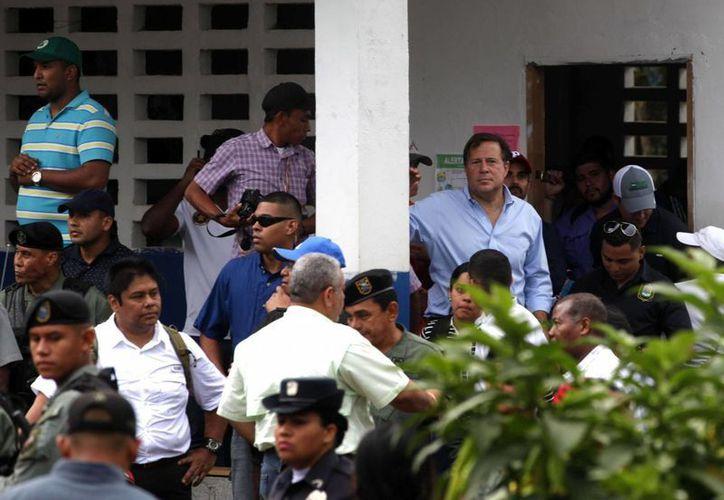 El presidente de Panamá, Juan Carlos Varela, (d), espera a que abran la puerta de un colegio donde quedó retenido por un grupo de indígenas descontentos con la firma de un acuerdo para la reactivación de un proyecto hidroeléctrico. (EFE)