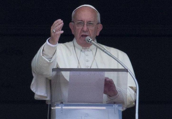 El Papa Francisco saluda desde la ventana de su estudio privado en el Palacio Apostólico del Vaticano, tras dirigir su oración del mediodía con el Angelus. (AP)