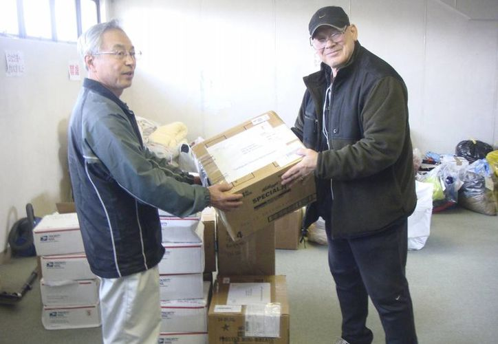En esta foto tomada el 13 de mayo de 2011, Joseph Roginski (d) sostiene un paquete en la municipalidad de Misawa, Japón. Un número creciente de estadounidenses se van al exterior al jubilarse. (Joseph Roginski vía AP)