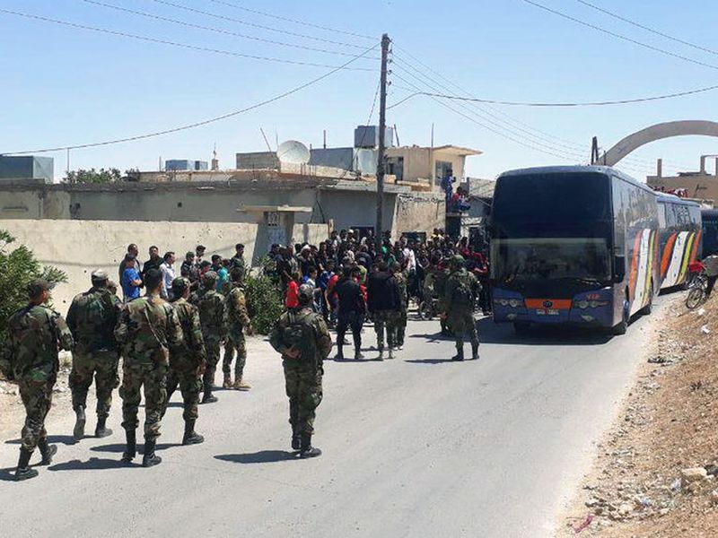 This photo released by the Syrian official news agency SANA, shows Syrian government forces overseeing the evacuation by bus of rebels and their family from the towns of Ruhaiba in the eastern Qalamoun region in the Damascus countryside, Syria.