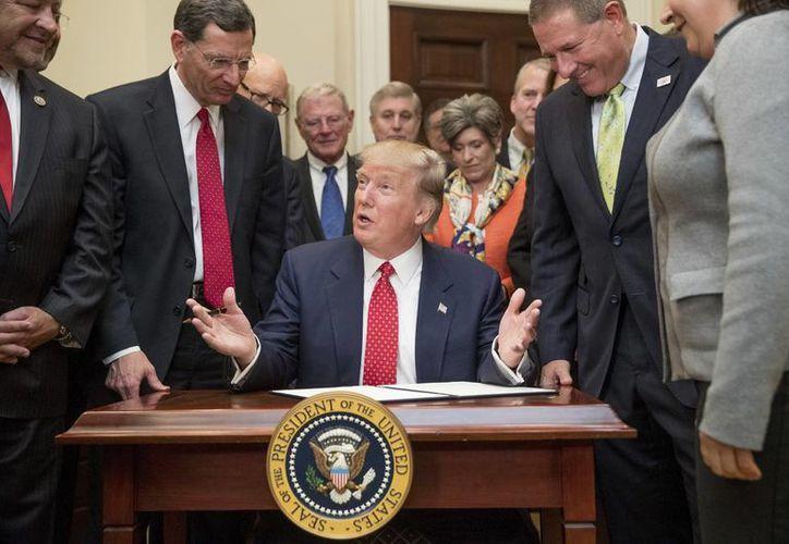 Trump firmó este martes la nueva norma que levanta la restricción de compra de armas a personas con padecimientos mentales. (AP/Andrew Harnik)