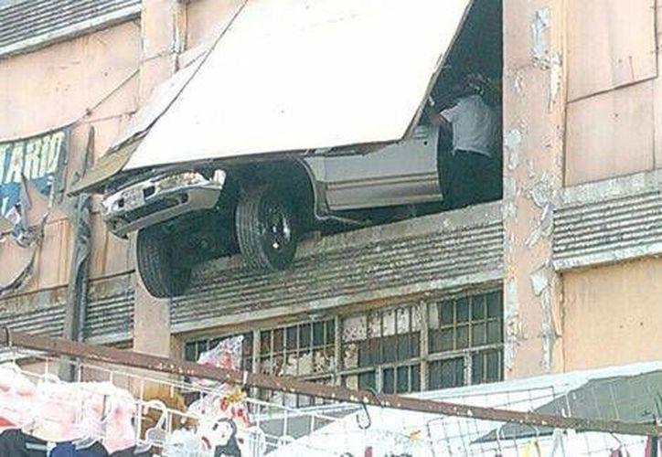 El conductor del vehículo fue detenido, pues por poco caía sobre unos puestos de ropa que había fuera del estacionamiento. (Milenio)
