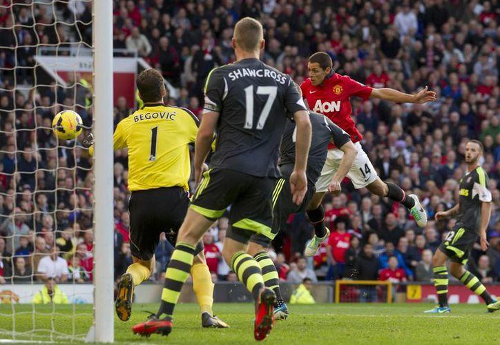 Hernández (d) marcó de cabeza el gol del triunfo para el Manchester United, que perdía en casa ante Stoke City. (Agencias)