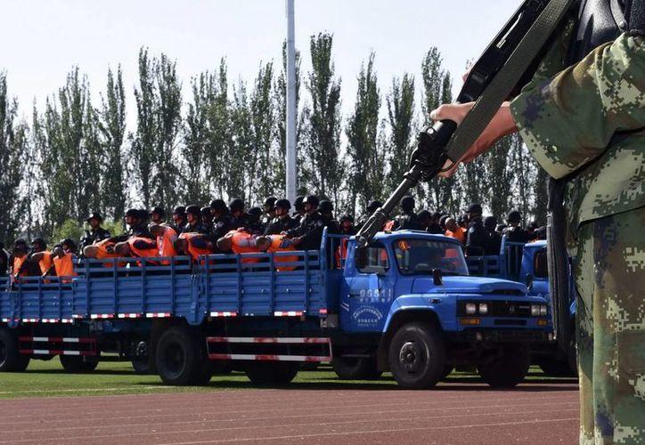 Un policía vigila durante la lectura pública de una sentencia a 55 criminales, y el anuncio de detención de 65 criminales sospechosos, el pasado mes de mayo en un estadio en la ciudad de Yining. (Archivo/EFE)