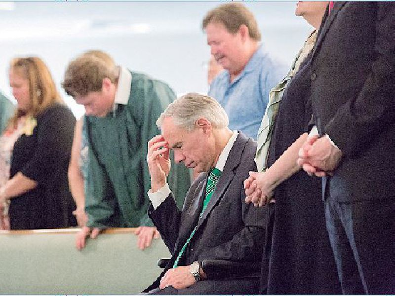 The Texas Gov. Greg Abbott joins a congregation in prayer at the Arcadia First Baptist Church, after a school shooting at Santa Fe High School on Friday, in Santa Fe, Texas.