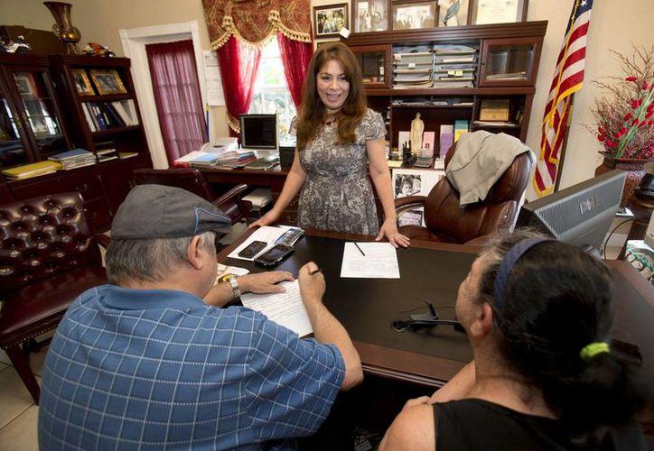 Nora Sándigo, al centro atrás, ayuda a Juan B. Salome, izquierda, de 70 años, y a su hermana Lourdes F. Salome, de 61 años, en algún trámite burocrático en Miami. (Agencias)
