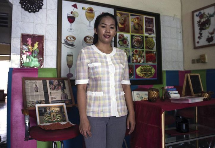 Lim Mouly Ratana, fundadora de la escuela Koun Brosar Srey (La Nuera), posa junto a pósteres de tallado de frutas y algunos artículos periodísticos sobre su escuela. (EFE)