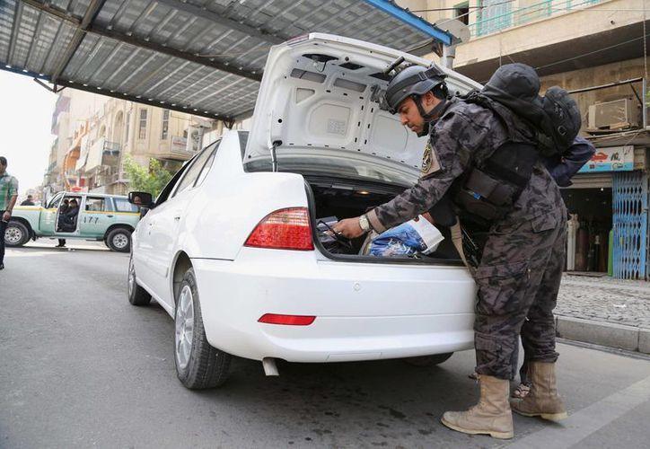 Un policía revisa un vehículo en Bagdad, donde las explosiones vehiculares son comunes. (Agencias)