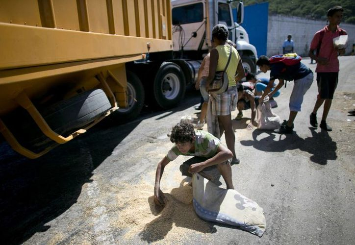 Un joven utiliza una funda de almohada para recoger arroz del pavimento caído de un camión de mercancías que espera para entrar en Puerto Cabello, Venezuela. (AP/Ariana Cubillos)