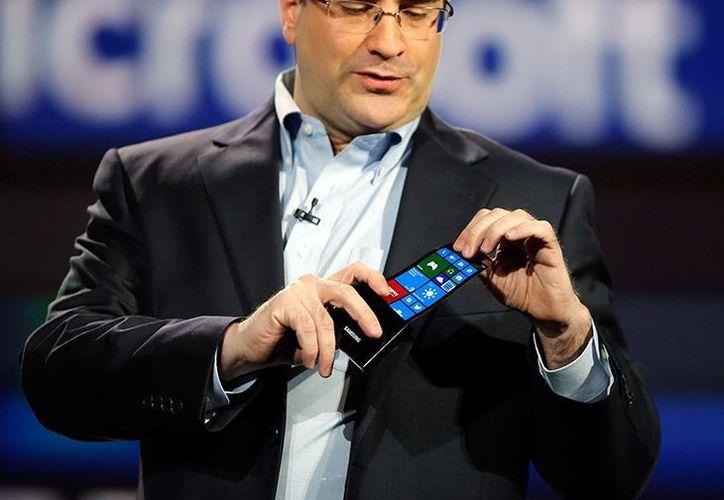 Un ejecutivo de Microsoft muestra una pantalla OLED flexible de un smartphone hecha por Samsung. (Agencias)