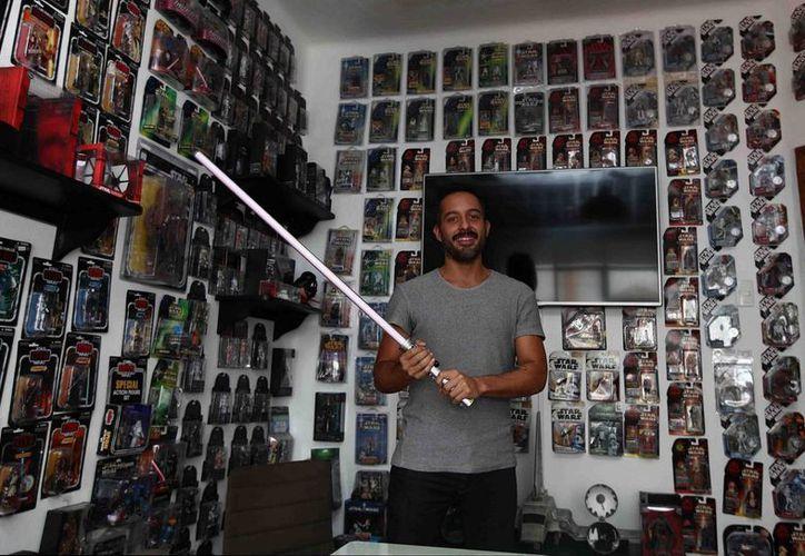 Nahim Quintana Hernández posa junto a sus más de tres mil objetos de Star Wars. (Notimex)