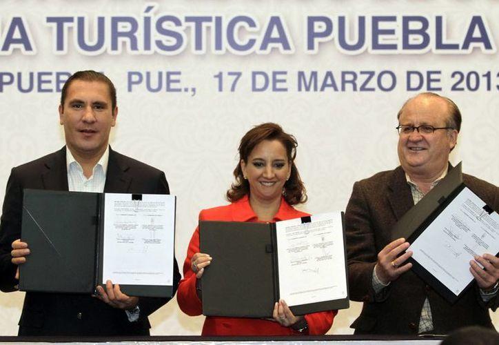 Los gobernadores de Puebla, Rafael Moreno, y Morelos, Graco Ramírez, firma un convenio con la secretaria de Turismo, Claudia Ruiz. (Notimex)