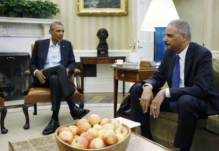 Fotografía de archivo del mes de agosto en la que se observa a el presidente Obama y a Eric Holder  en la Oficina Oval de la Casa Blanca en Washington. (Agencias)