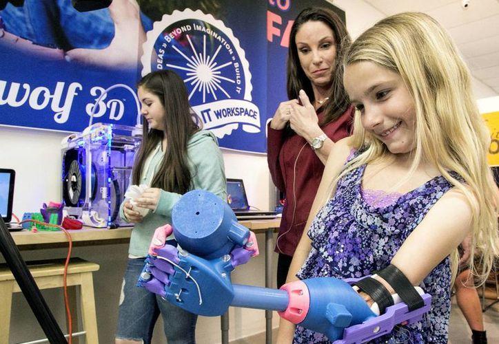 Faith Lennox sonríe mientras sostiene con su prótesis un objeto de plástico. (Agencias)