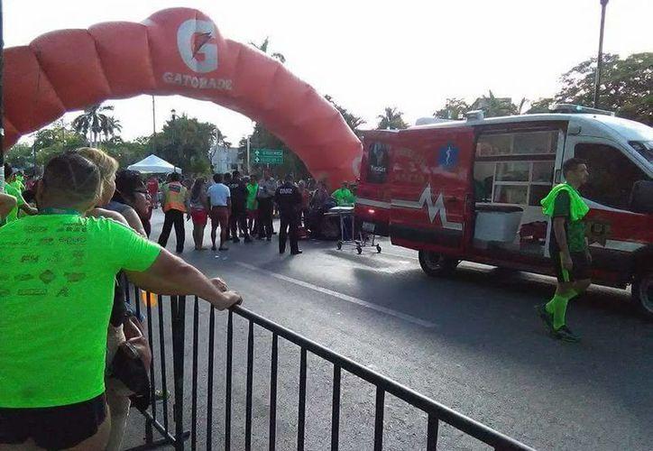 Imagen de los paramédicos mientras atendían al menor lesionado. La estructura de la meta final de la Carrera del Pavo se desplomó sobre un niño. (Foto de AD Mérida)