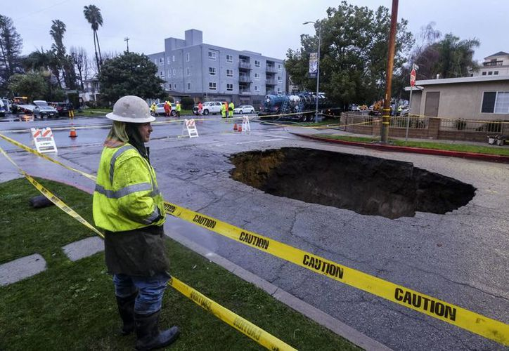 Inspectores examinan un socavón en Studio City, al norte de Los Ángeles, California, luego de tormentas que afectaron el estado. (AP/Ringo H.W. Chiu)