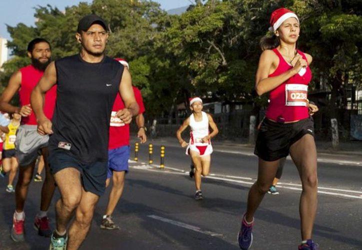 Los corredores portarán gorro navideño o corona, y barba de Santa Claus. Imagen de la carrera del año pasado en Mérida. (Milenio Novedades)