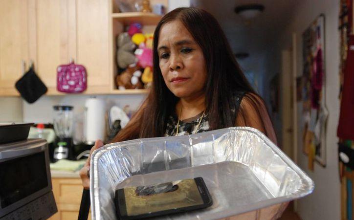 Una mujer muestra su smartphone Galaxy Note 7 de sustitución en una bandeja de aluminio en su casa en Honolulu, un día después de que arrojase humo. (AP/Audrey McAvoy)