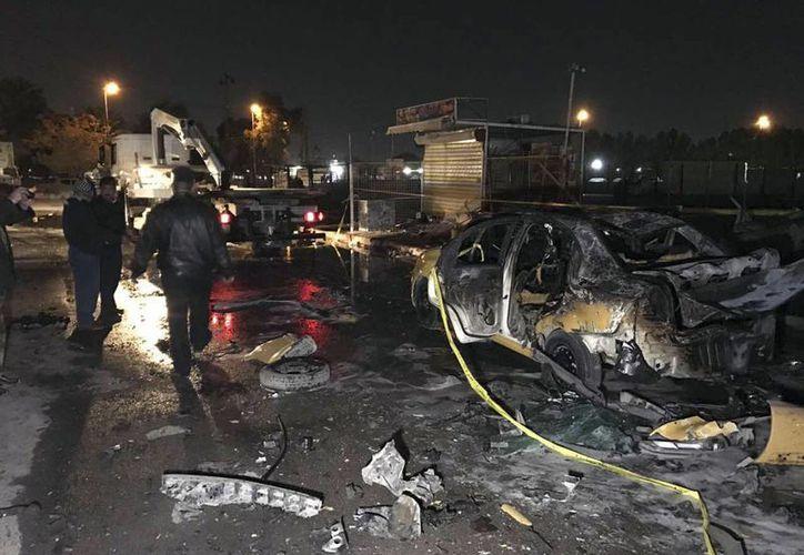 Las fuerzas de seguridad iraquíes se reúnen en el lugar de un atentado con coche bomba suicida en Bagdad, Irak. Al menos a 10 muertos y 30 heridos han dejado los dos últimos atentados. (Foto de AP / Ali Abdul Hassan)