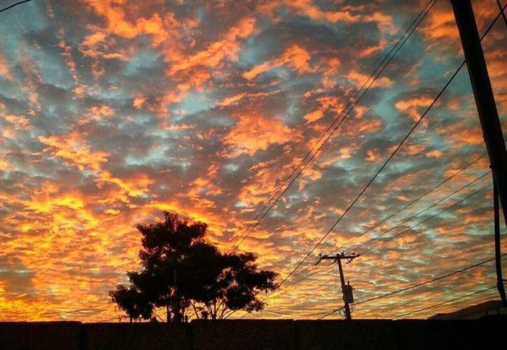 El aspecto rojizo del cielo tomó por sorpresa a los yucatecos este martes al amanecer. (Carlos Benítez/SIPSE)