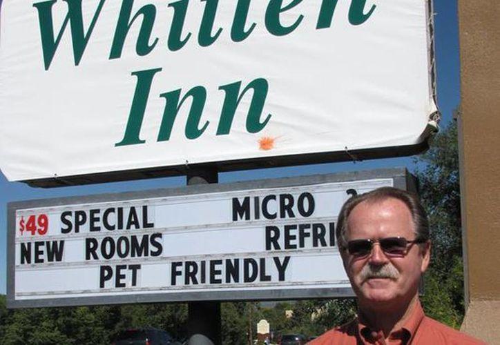 El propietario de la cadena Whitten Inn, Larry Whitten, en imagen de 2009, posando a un lado de la publicidad de su hotel en Taos, Nuevo México. (Agencias)