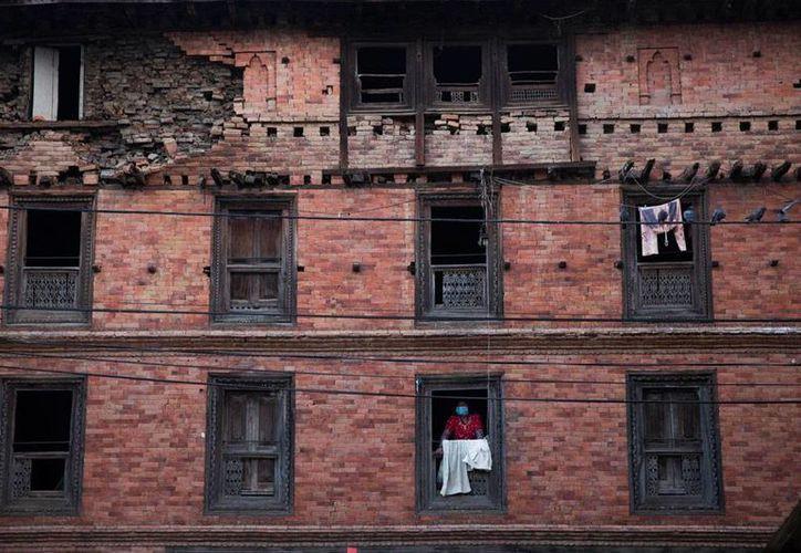 Unos mil ingenieros civiles revisan casa por casa 13,000 viviendas en Nepal, donde un sismo de magnitud 7.8 causó daños en cientos de estructuras. La imagen corresponde a un edificio habitacional en Sakhu. (AP)
