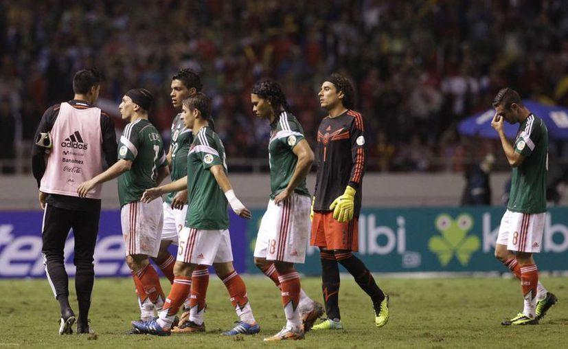 Los jugadores mexicanos abandonan cabizbajos el terreno de juego, pese a que el triunfo de EU les dio vida. (Agencias)