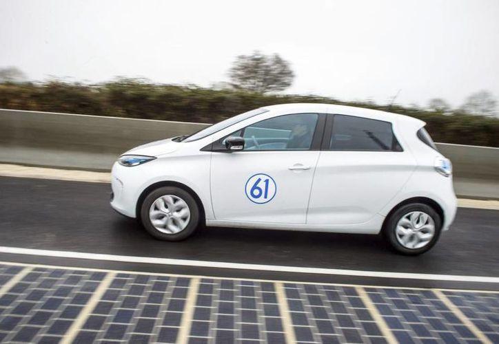 Un coche eléctrico conduce en la primera carretera equipada con paneles solares, en Tourouvre au Perche, Francia. (El País)