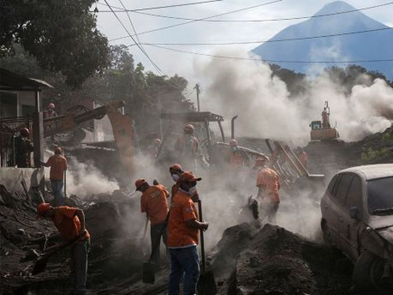"Rescue workers remove piles of ash spewed by the Volcan de Fuego, or ""Volcano of Fire,"" eruption, in El Rodeo, Guatemala."