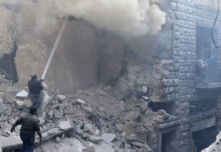 Unos civiles tratan de sofocar un incendio desencadenado tras un ataque aéreo por parte del régimen sirio en el barrio de Kalase en Alepo, en febrero pasado. (EFE/Archivo)