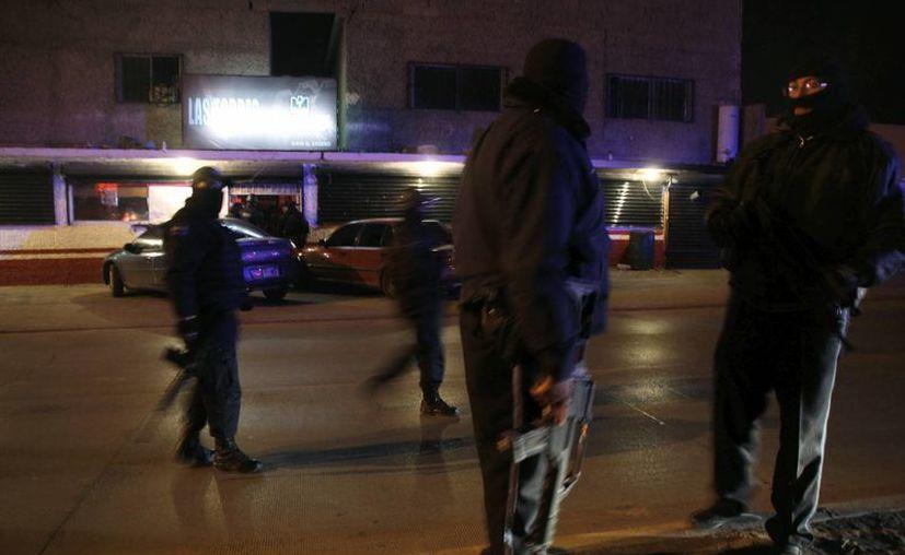 Agentes federales resguardan la zona donde un grupo de sicarios irrumpió en un bar de México. (Archivo/EFE)