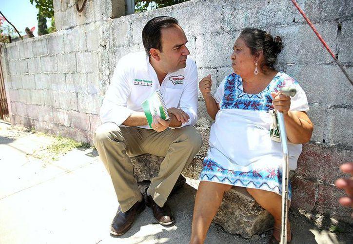 El candidato del PRI a la alcaldía platica con una vecina de Molas, durante su recorrido proselitista. (SIPSE)